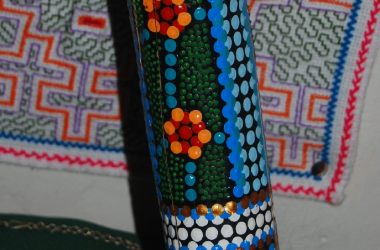 Detail of Decoration of a Didgeridoo against an Hallucinogenic Weaving of the Shipibo Indians