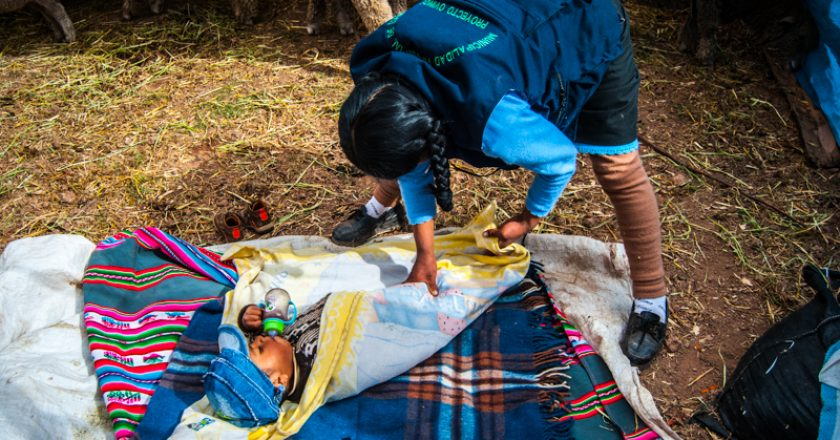 A Mother Wrapping Her Baby on the Floor (Photo: Walter Coraza)